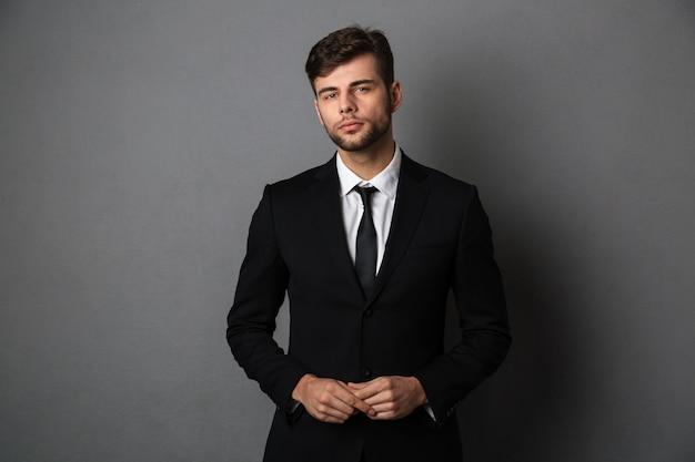 Photo en gros plan de jeune homme d'affaires prospère en costume noir