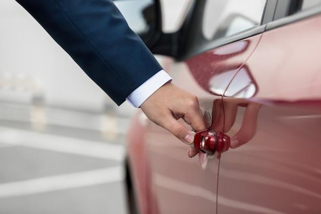 Photo gros plan d'un jeune homme d'affaires tirant la poignée de porte de voiture