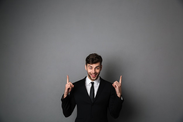 Photo en gros plan d'un jeune homme souriant en tenue de soirée pointant avec deux doigts vers le haut