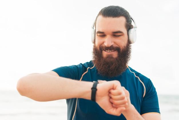 La photo en gros plan d'un jeune homme sportif barbu utilisant une montre connectée près de la plage, un coureur