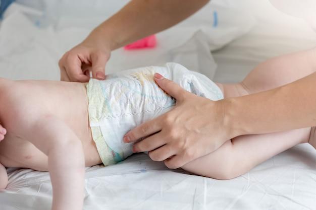Photo gros plan d'une jeune mère qui change la couche de son bébé