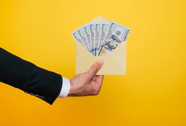 La photo en gros plan de jeunes mains masculines tenant le grand nombre de dollars des états-unis isolés sur fond jaune