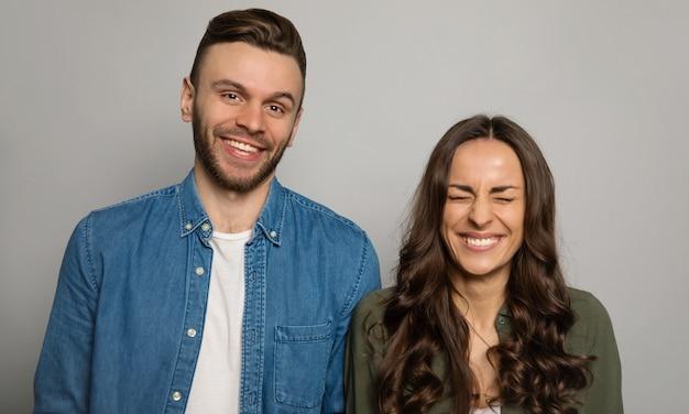 Photo en gros plan d'un joli couple en tenue de tous les jours, debout devant la caméra et riant de joie.