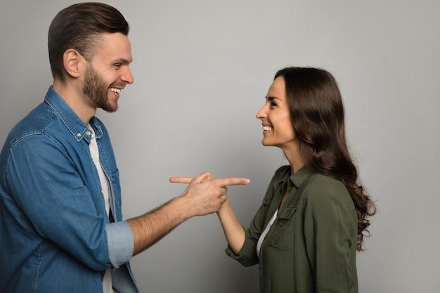 Photo en gros plan d'un joli couple en tenue de tous les jours, qui pose de profil, se regarde dans les yeux, sourit et se montre du doigt