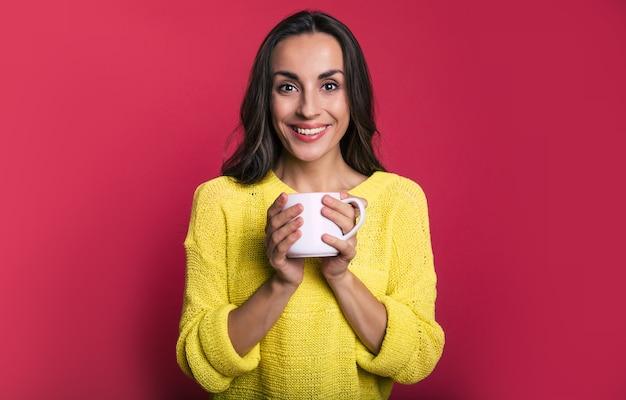 Photo en gros plan d'une jolie brune vêtue d'un pull jaune, qui regarde dans l'appareil photo avec un sourire ouvert et tient une tasse de thé blanc dans ses mains