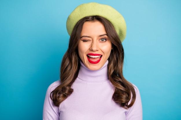 Photo gros plan de jolie dame bonne humeur lèvres rouges personne coquette clignotant un œil voir beau mec porter chapeau béret vert col roulé violet isolé mur de couleur bleu