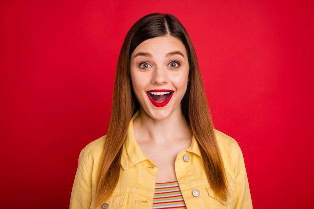 Photo en gros plan d'une jolie dame drôle et brillante pommade brillante écouter des nouvelles incroyables bouche ouverte bonne humeur porter une veste de blazer en jean jaune décontractée isolée sur fond de couleur rouge vif