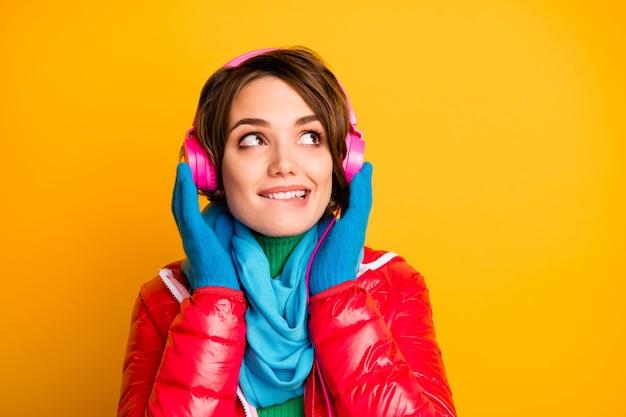 Photo gros plan de jolie dame mordre la lèvre écouter des écouteurs modernes à la recherche d'un espace vide intéressé porter des gants de foulard bleu pardessus rouge casual
