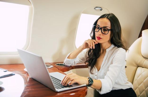 Photo en gros plan d'une jolie femme en blouse blanche et lunettes, qui tape quelque chose sur son ordinateur portable, sourit et regarde dans la caméra alors qu'elle est assise sur son siège côté hublot dans un avion.