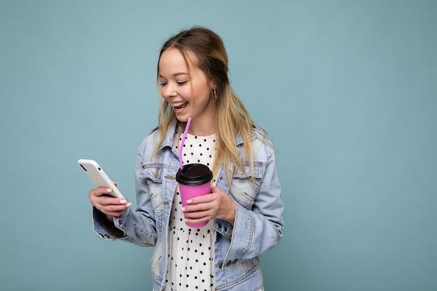 Photo en gros plan d'une jolie femme magnifique en veste de jean souriante et tenant un smartphone en buvant