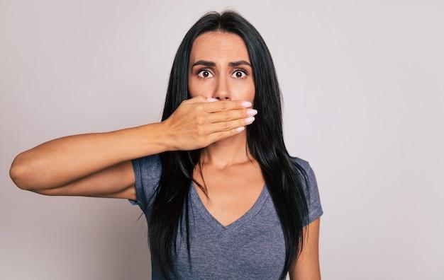 Photo en gros plan d'une jolie fille brune avec une expression de visage inquiet, qui se tient devant la caméra avec sa main droite couvrant sa bouche