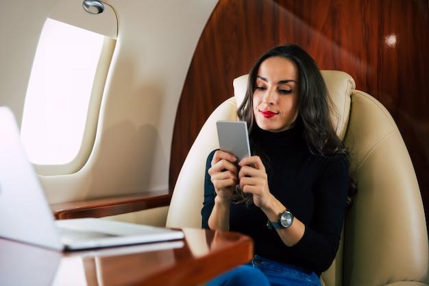 Photo en gros plan d'une jolie fille vêtue d'une tenue décontractée, qui lit quelque chose sur son smartphone, tout en prenant un vol confortable à bord d'un avion de première classe.