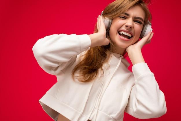 Photo gros plan d'une jolie jeune femme blonde souriante et positive portant un sweat à capuche blanc isolé sur