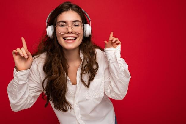 Photo gros plan d'une jolie jeune femme brune souriante et positive portant une chemise blanche et optique