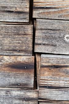 Une photo en gros plan d'une jonction de planches qui sont le mur d'une ancienne grange en bois à la campagne