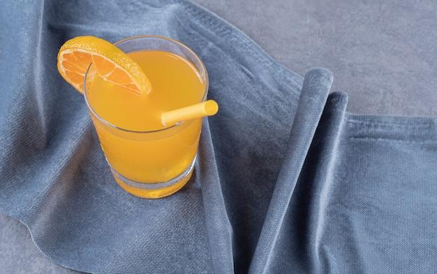 La photo en gros plan de jus d'orange fraîchement préparé sur fond gris.
