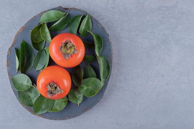 La photo en gros plan de kaki frais avec des feuilles sur planche de bois