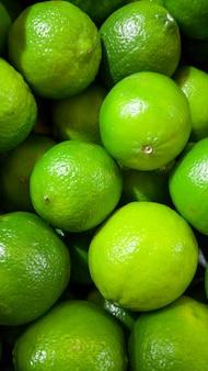 Photo gros plan de limes vertes avec ogm allongé sur le comptoir au magasin. gros plan texture ou motif de fruits mûrs frais. beau fond de nourriture