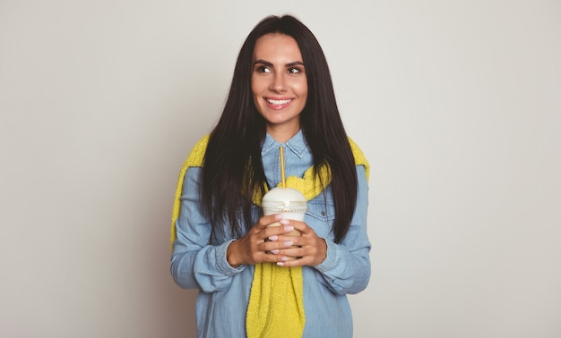 Photo en gros plan d'une magnifique jeune femme aux longs cheveux noir de jais, qui regarde vers la gauche et tient son café dans ses mains