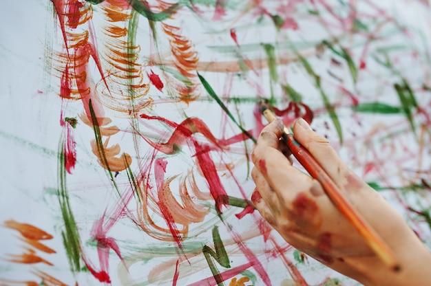Photo en gros plan d'une main féminine peignant sur le papier à l'aquarelle.