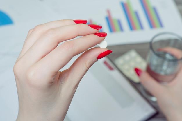 La photo en gros plan de la main de la femme tenant la pilule et le verre