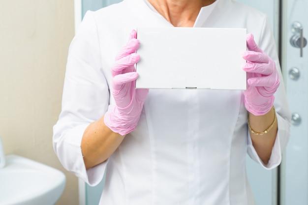 Photo gros plan des mains du cosmétologue tenant une boîte blanche avec des charges. concept de soins de santé, médical et pharmacie. maquette pour votre projet