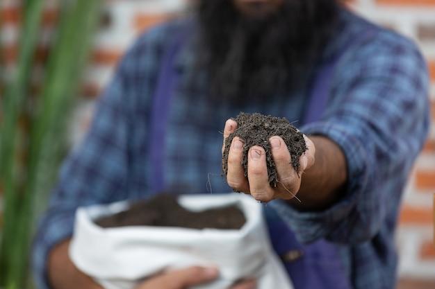Photo gros plan des mains du jardinier tenant le sol