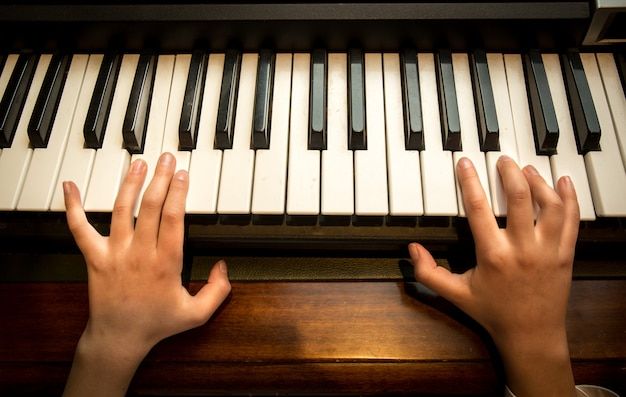 Photo gros plan des mains de l'enfant jouant au piano
