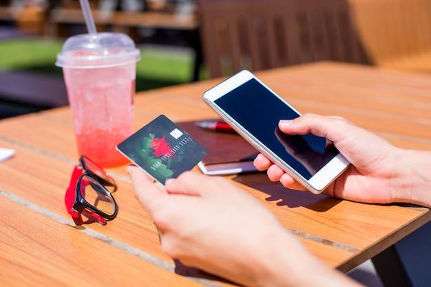 La photo en gros plan des mains féminines à l'aide de smartphone et carte de crédit pour les achats en ligne