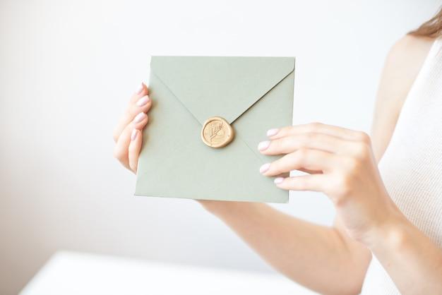 Photo gros plan de mains féminines tenant l'enveloppe d'invitation avec un sceau de cire, un certificat-cadeau, une carte postale, une carte d'invitation de mariage.