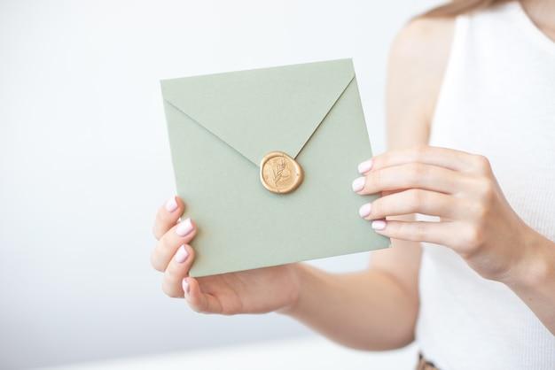 Photo en gros plan de mains féminines tenant une enveloppe d'invitation avec un sceau de cire, un chèque-cadeau, une carte postale, une carte d'invitation de mariage.