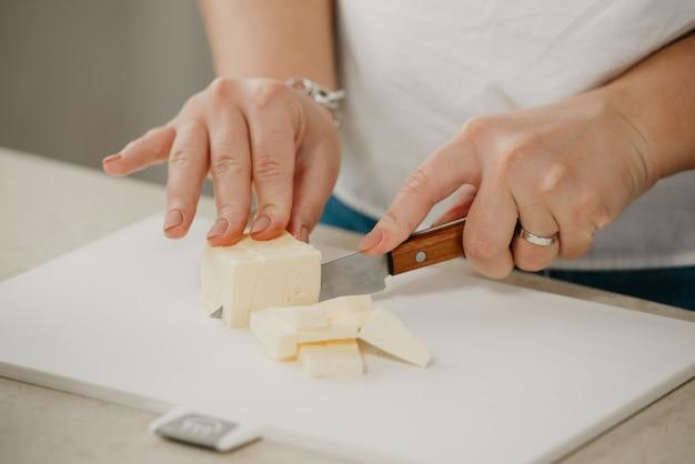 Ð photo en gros plan des mains d'une jeune femme qui coupe du beurre frais sur une planche à découper avec un couteau bien aiguisé.