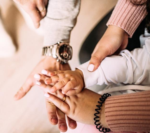 Photo gros plan des mains d'une petite fille enfant et ses parents les mains sont au-dessus de l'autre famille