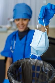 Une photo en gros plan d'un masque facial usagé a été jetée dans une poubelle de sac à ordures par une femme médecin souriante et heureuse en uniforme d'hôpital bleu, des gants en caoutchouc et un stéthoscope sur fond flou après la fin de la pandémie.