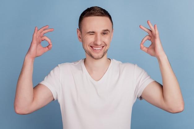La photo en gros plan d'un mec séduisant tenant la main montrant des symboles okey clin d'oeil arrière-plan de couleur bleu isolé