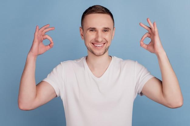 La photo en gros plan d'un mec séduisant tenant la main montrant des symboles okey exprimant un accord souriant à pleines dents porter un t-shirt rose décontracté isolé sur fond de couleur bleu