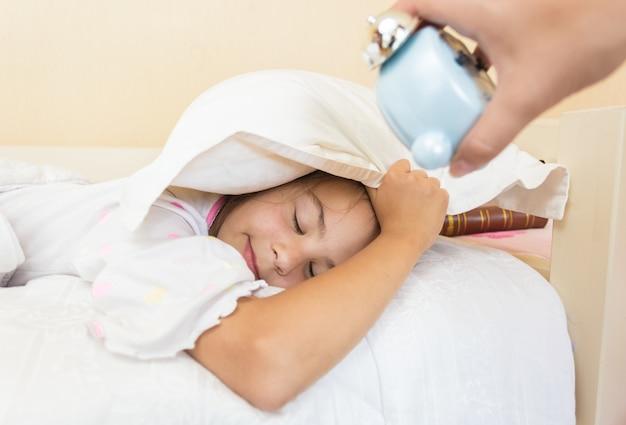 Photo gros plan d'une mère tenant un réveil sur l'oreille des filles endormies