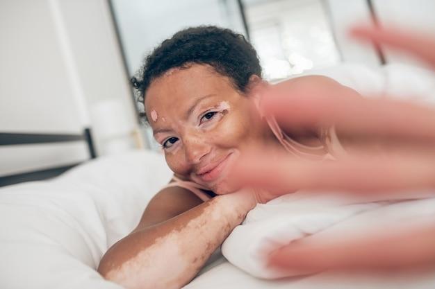 Une photo en gros plan d'une mignonne mulâtre au lit