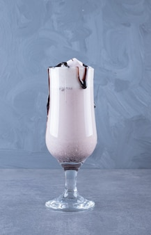 La photo en gros plan de milk-shake au chocolat fraîchement préparé sur fond gris.