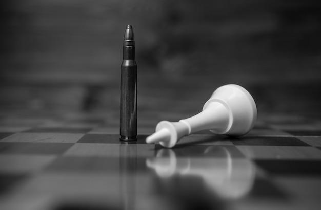 La photo en gros plan en noir et blanc de la balle gagne le jeu d'échecs. concept de puissance des armes à feu
