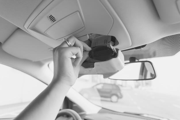 Photo en gros plan noir et blanc d'une femme prenant des lunettes de soleil dans le compartiment de la voiture