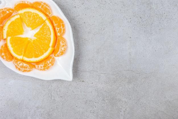 La photo en gros plan d'orange et de mandarine en tranches sur une plaque blanche.