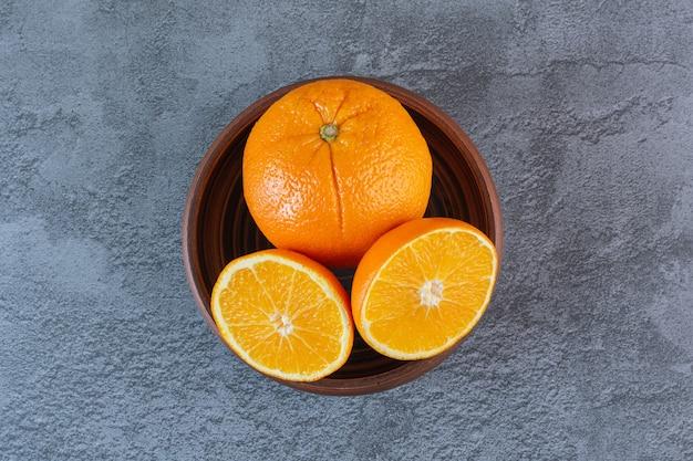 La photo en gros plan d'oranges biologiques dans un bol en bois.