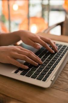 Photo en gros plan d'un ordinateur portable moderne et d'une femme mettant les deux mains sur le clavier tout en l'utilisant