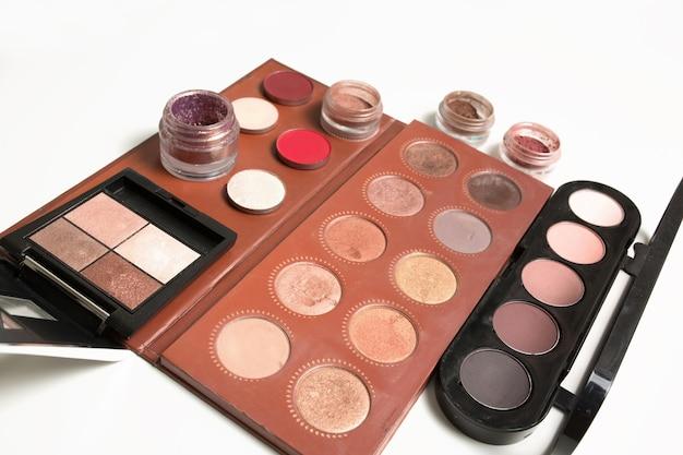 Photo en gros plan de palettes de maquillage professionnel avec des pigments pour les yeux et des paillettes sur fond blanc