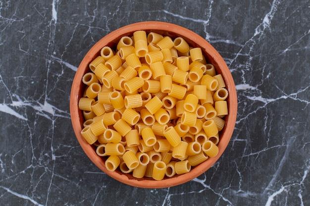 La photo en gros plan de pâtes penne dans un bol de poterie.