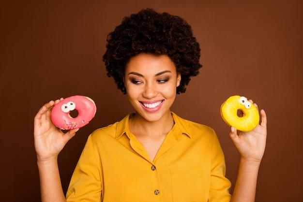 Photo gros plan de la peau foncée funky dame tenir deux beignets colorés yeux caramel visages humains peinture choisir quoi manger en premier porter chemise jaune couleur marron