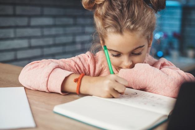 La photo en gros plan d'une petite fille blonde dessinant quelque chose dans son cahier assis à la table dans la cuisine
