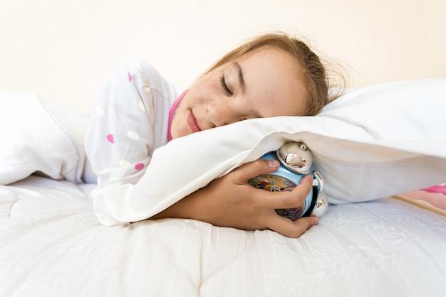 Photo gros plan d'une petite fille endormie et tenant un réveil sous un oreiller