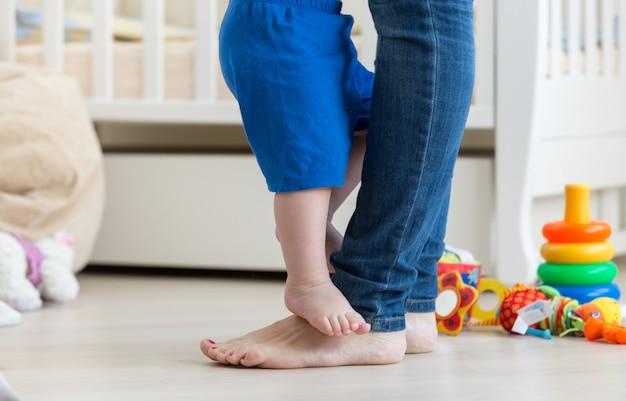 Photo gros plan des pieds de bébé debout devant les pieds de la mère sur le sol